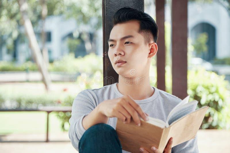 Individuo asiático con el libro que se relaja en parque fotos de archivo