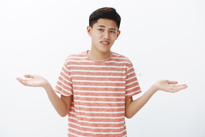 Individuo asiático joven atractivo vacilante con el pelo oscuro que encoge las manos de extensión de lado como tomar la opción du foto de archivo