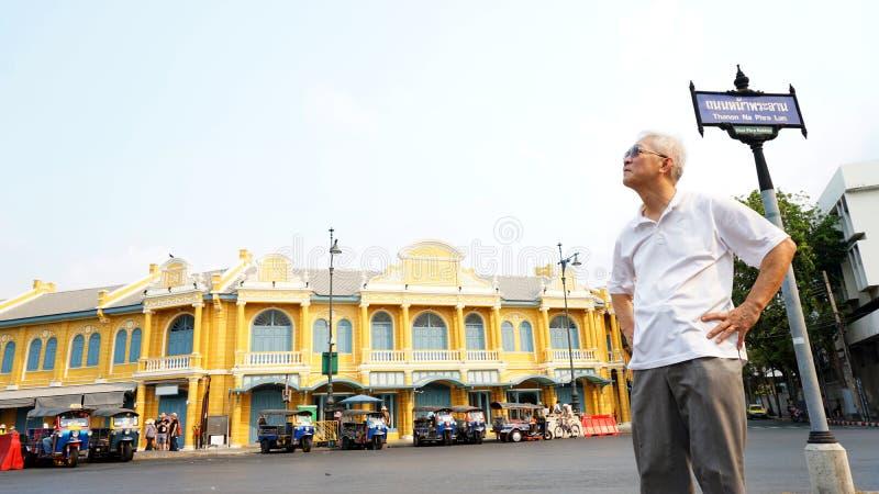 Individuo asiático mayor delante de la arquitectura tailandesa clásica en na PHR imagenes de archivo