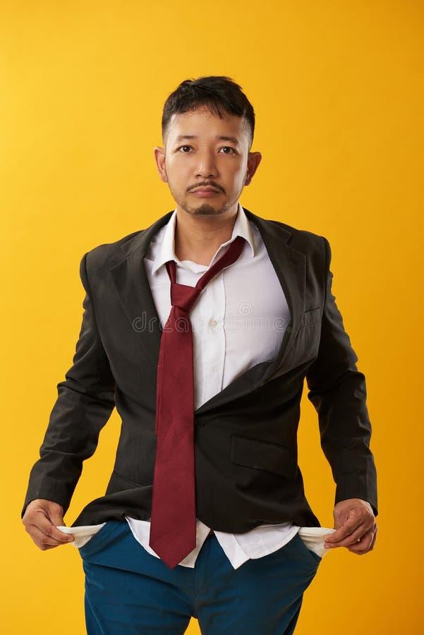 Individuo asiático sin el dinero en bolsillos foto de archivo