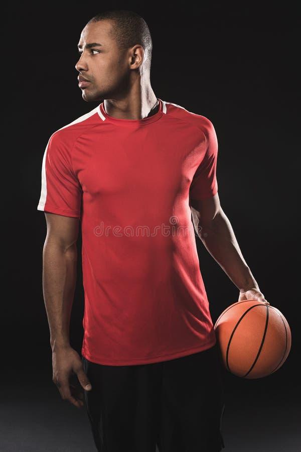 Individuo atlético con la bola que gira detrás imagen de archivo
