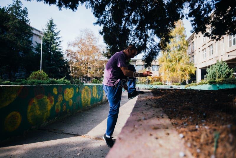 Individuo atlético de Parkour que hace salto mortal hacia atrás y trucos mientras que salta y sobre de un muro de cemento foto de archivo libre de regalías