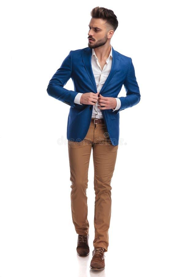 Individuo atractivo en el traje que abotona su chaqueta y caminar de salón imagen de archivo