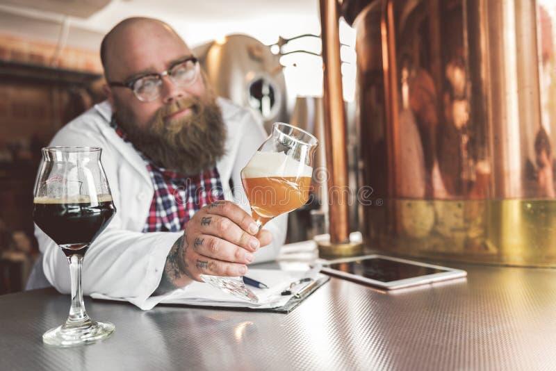 Individuo barbudo gordo que se coloca en los envases del metal con sonrisa leve imagen de archivo libre de regalías