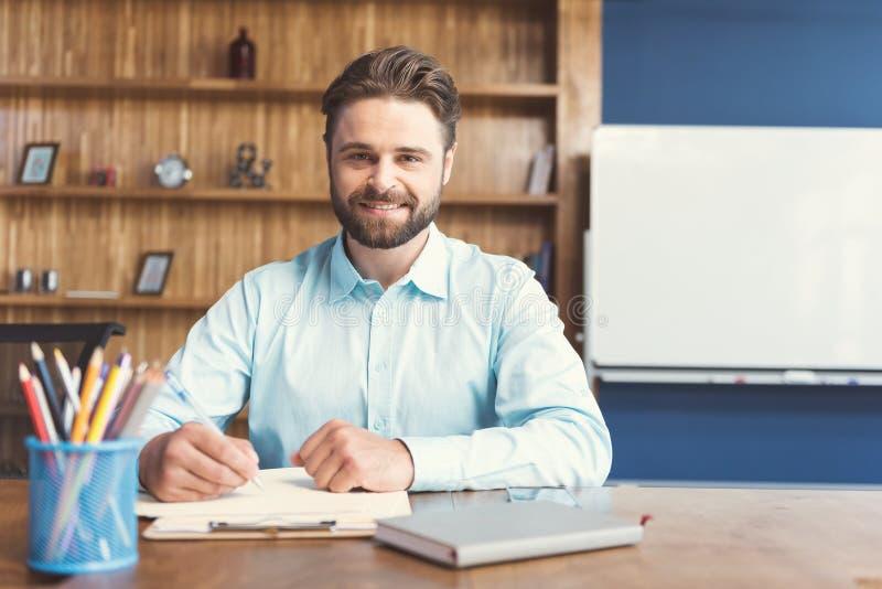 Individuo barbudo joven alegre que realiza tarea formal en oficina fotos de archivo libres de regalías