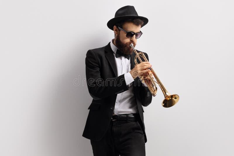 Individuo barbudo que toca una trompeta fotografía de archivo libre de regalías