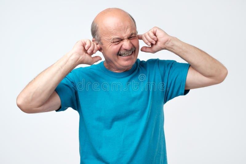 Individuo calvo hispánico mayor que tapa los oídos con los fingeres que oyen sonidos ruidosos de la música foto de archivo
