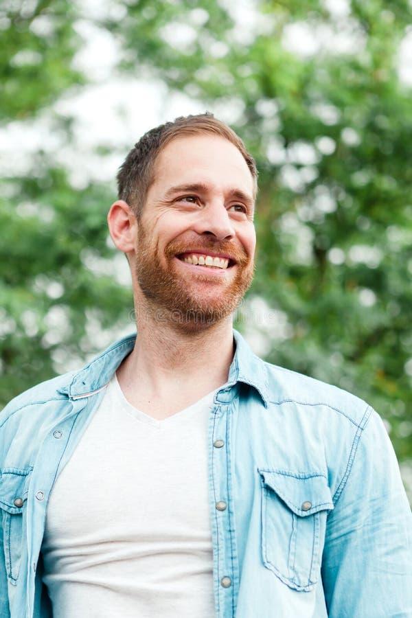 Individuo casual con una camisa del dril de algodón en un parque fotos de archivo