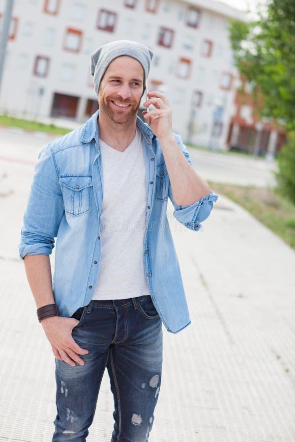 Individuo casual de la moda que llama con su móvil foto de archivo