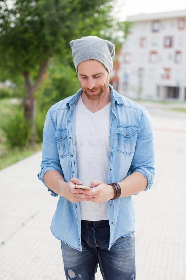 Individuo casual de la moda que toma un paseo con su móvil imagen de archivo
