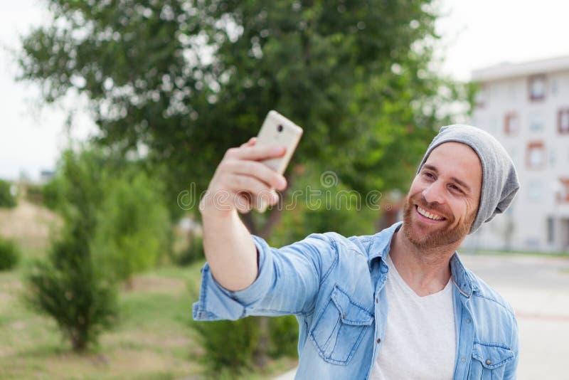 Individuo casual de la moda que toma una foto con un móvil en la ciudad foto de archivo libre de regalías