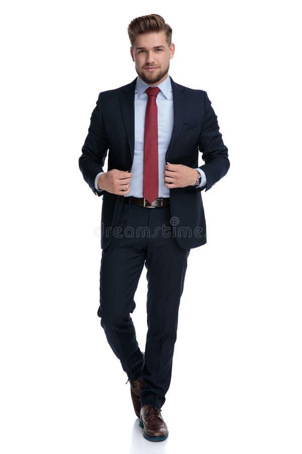 Individuo casual motivado que camina y que fija su chaqueta fotografía de archivo