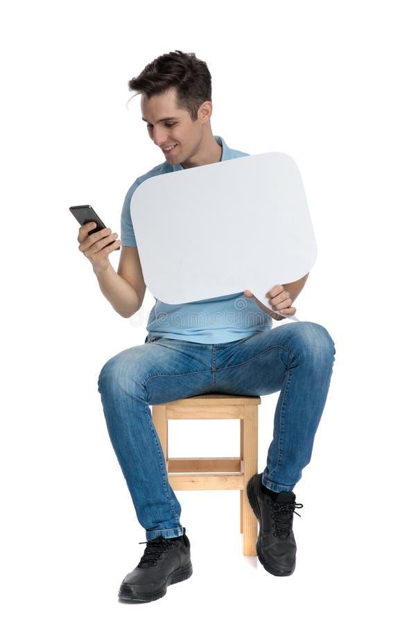 Individuo casual que manda un SMS y que lleva a cabo a una burbuja en blanco del discurso fotos de archivo