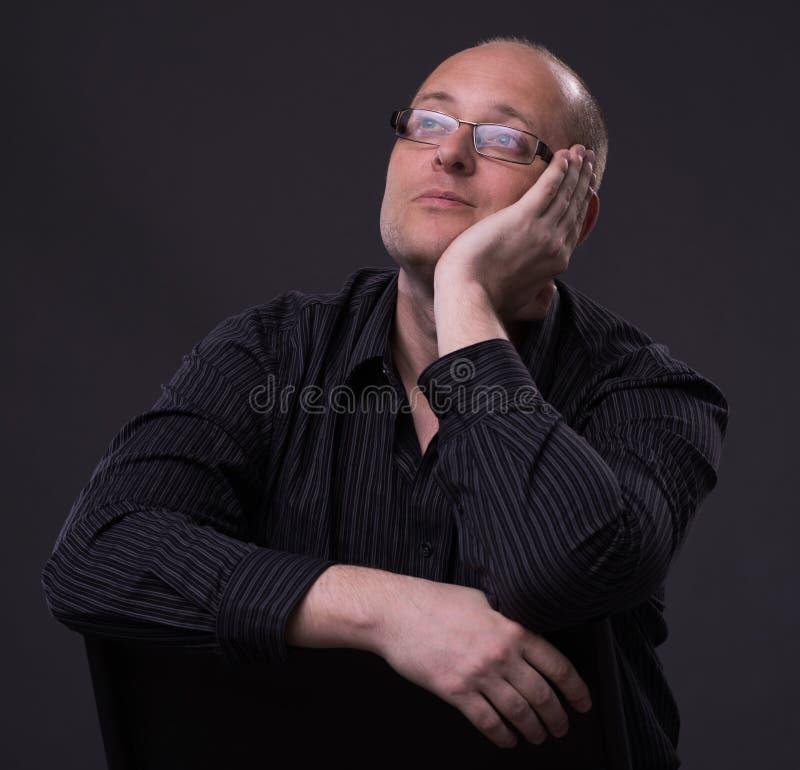 Individuo caucásico aburrido que se sienta en una silla imágenes de archivo libres de regalías