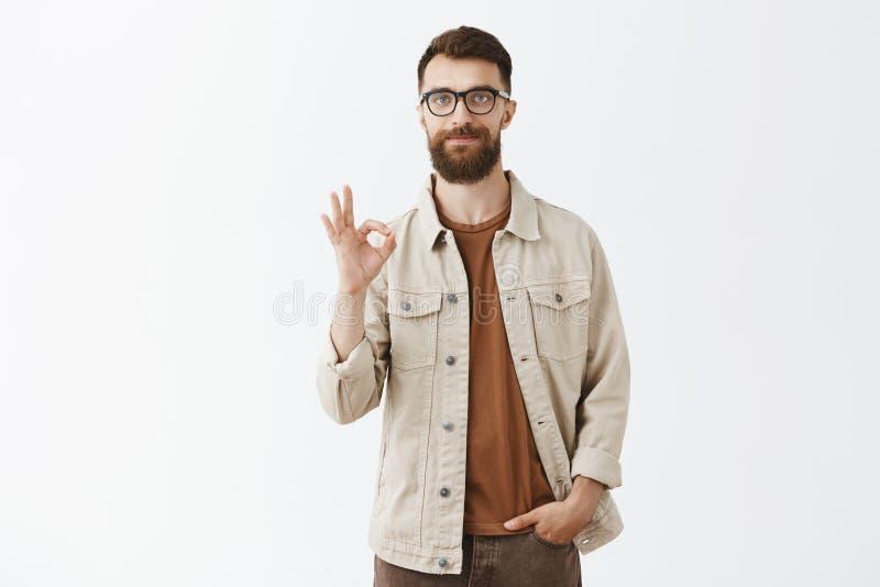 Individuo caucásico hermoso amistoso tranquilo con el peinado largo de la barba y del cortocircuito que muestra gesto excelente o imagen de archivo libre de regalías