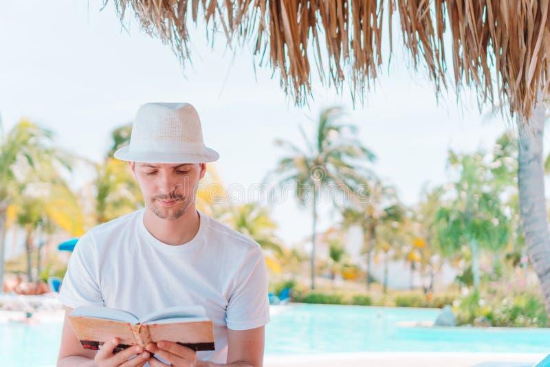 Individuo caucásico que se relaja cerca de piscina con el libro de la visión que sorprende y de lectura imagen de archivo libre de regalías