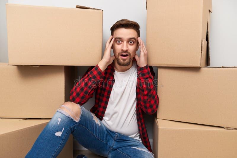 Individuo chocado cerca de las cajas del cartón foto de archivo libre de regalías