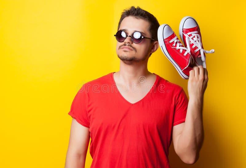 Individuo con las gafas de sol y los gumshoes rojos imagen de archivo