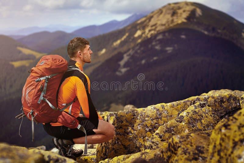 Individuo con una mochila del viaje en el top de un canto rodado fotografía de archivo