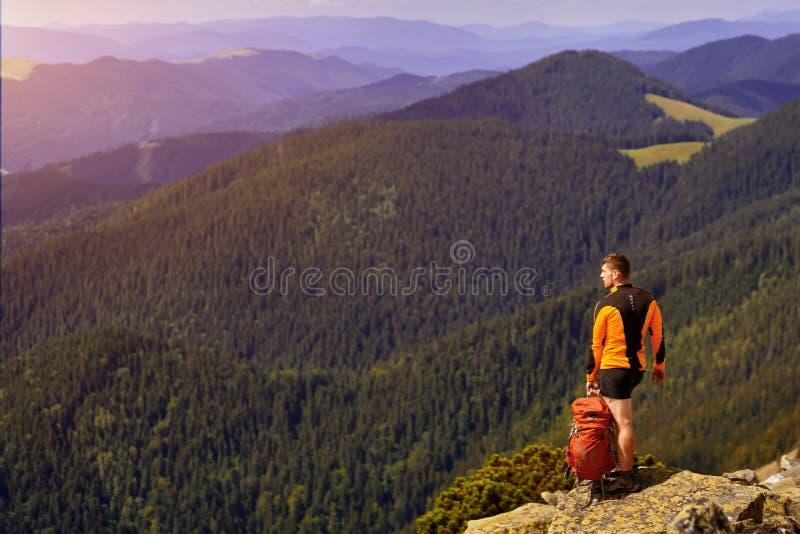 Individuo con una mochila del viaje en el top de un canto rodado fotografía de archivo libre de regalías