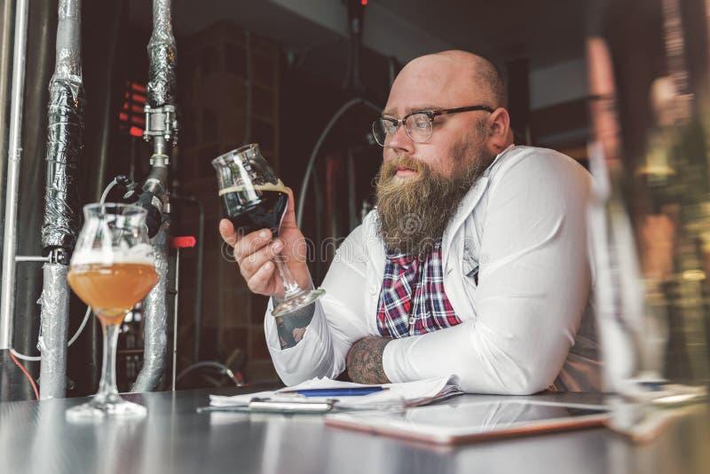 Individuo confiado que trabaja con la concentración mientras que se coloca en cervecería fotografía de archivo libre de regalías