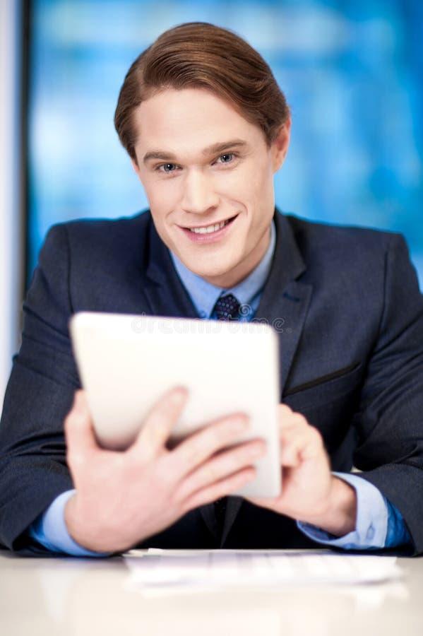 Individuo corporativo que hojea en la PC de la tableta fotografía de archivo