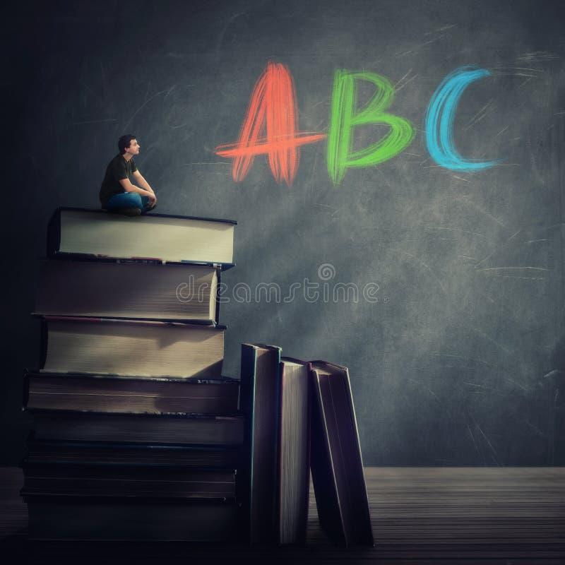 Individuo curioso del estudiante asentado en el top de un atack enorme de los libros que miran la pizarra con las letras de ABC e foto de archivo libre de regalías