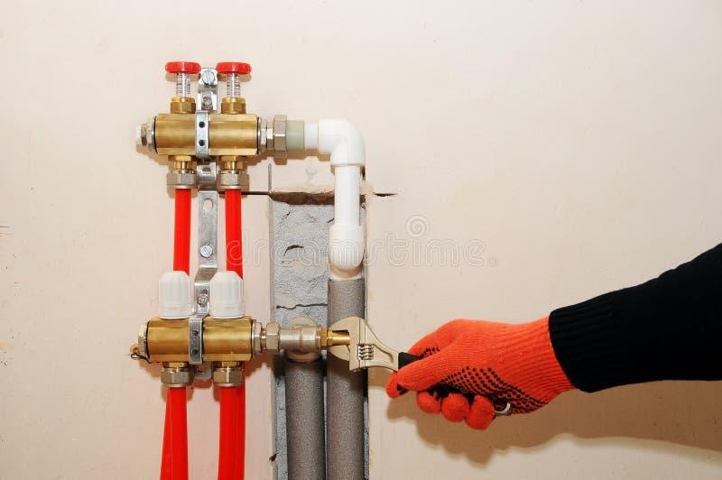 Individuo de la instalación de la calefacción de casa Un fontanero ata el tubo a la calefacción del colector Instalación de la ca imágenes de archivo libres de regalías