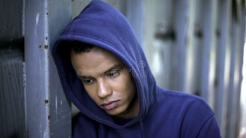 Individuo de la raza mixta que sufre de tiranizar, discriminación racial, juventud cruel foto de archivo