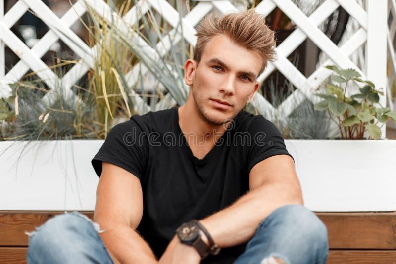 Individuo de moda hermoso con un peinado en una camiseta negra fotos de archivo