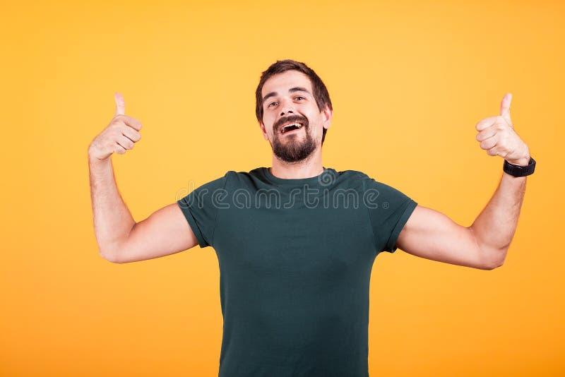 Individuo de moda sonriente feliz que muestra los pulgares para arriba imagen de archivo