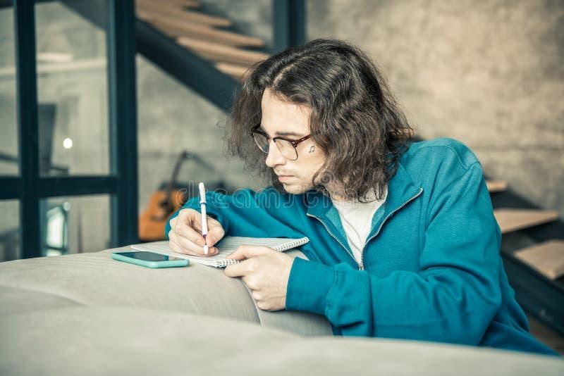 Individuo de pelo largo atento con el pelo largo que reescribe notas en álbum imagenes de archivo
