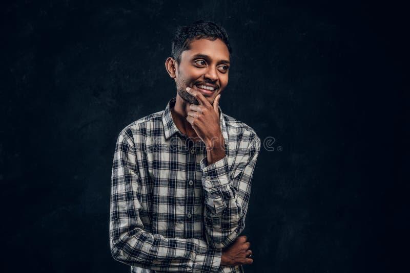 Individuo de piel morena en camisa que sonríe y que plantea la situación fotos de archivo libres de regalías