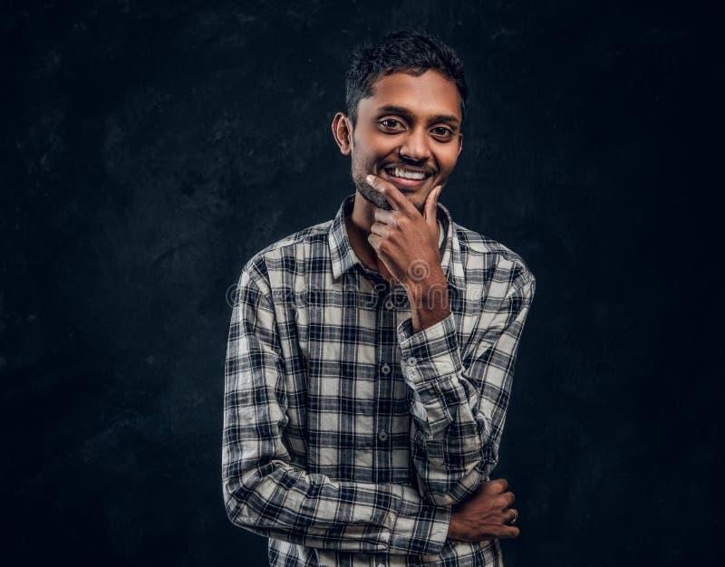 Individuo de piel morena joven en camisa que sonríe y que plantea la situación, mirando en la cámara imagenes de archivo