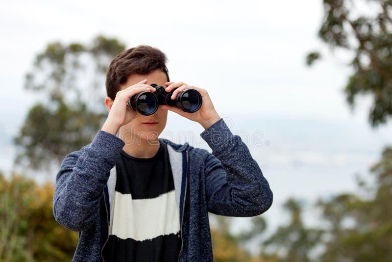 Individuo del adolescente que mira con los prismáticos foto de archivo
