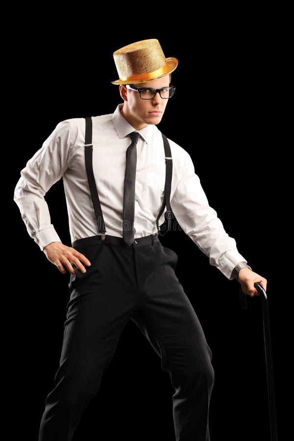 Individuo elegante con el sombrero que celebra un bastón y una presentación imagenes de archivo