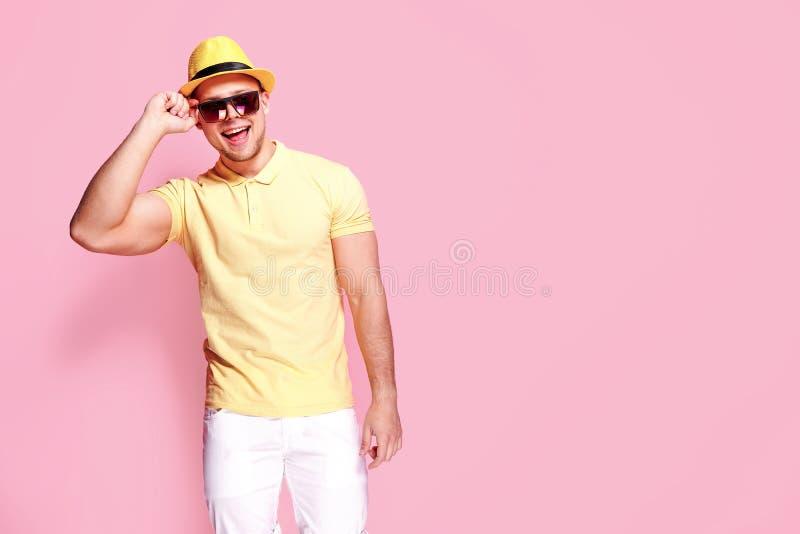 Individuo elegante confiado en la camisa amarilla, gafas de sol, pantalones cortos blancos, sombrero de paja que mira la cámara foto de archivo