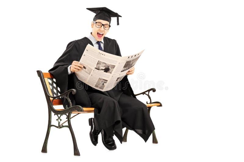 Individuo emocionado en vestido de la graduación que lee un periódico asentado en ben foto de archivo
