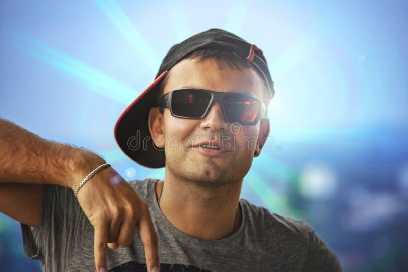Individuo enérgico joven en una gorra de béisbol y las gafas de sol activamente MES imagenes de archivo