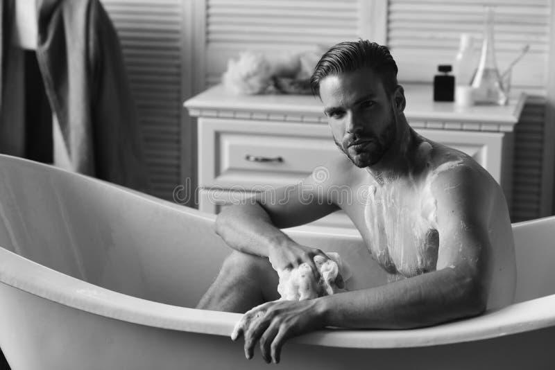 Individuo en cuarto de baño con los artículos de tocador y silla con la chaqueta en fondo Hombre con la barba y la cara seria que fotos de archivo libres de regalías