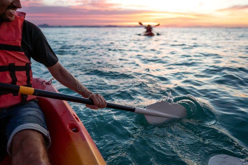 Individuo en kajaks en el mar en la puesta del sol foto de archivo libre de regalías