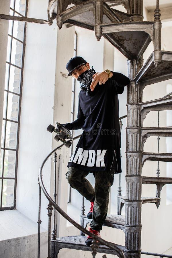 Individuo en la máscara que sostiene el monopatín imagen de archivo