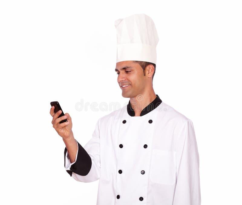 Individuo encantador en mandar un SMS uniforme del cocinero en el teléfono móvil fotos de archivo libres de regalías