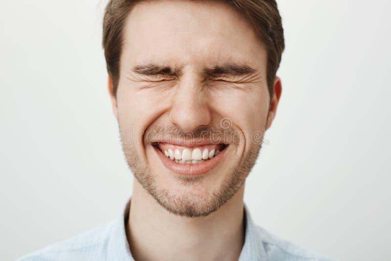 Individuo europeo feliz emotivo con la cerda que se coloca con los ojos firmemente cerrados, bizqueando y sonriendo ampliamente,  fotografía de archivo