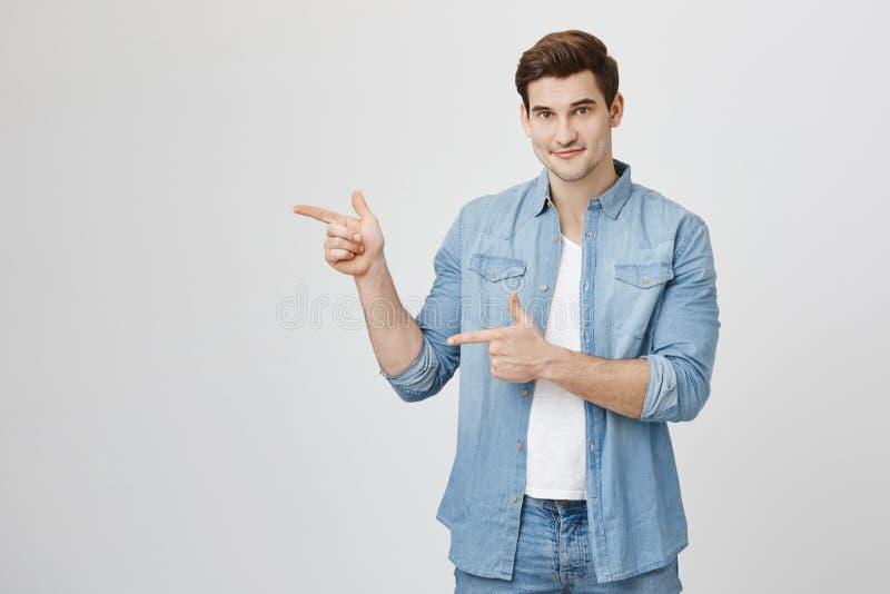 Individuo europeo hermoso apuesto con corte de pelo de moda y sonrisa sincera que señala los dedos índices, haciendo gesto del ar fotos de archivo