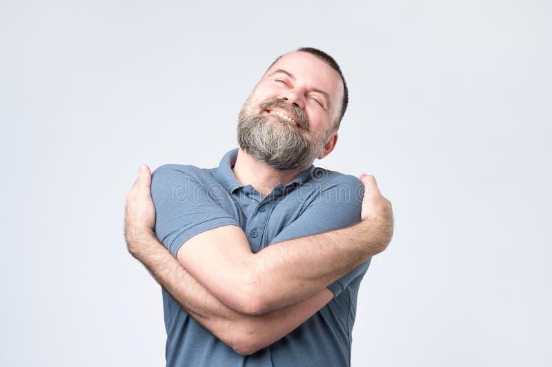 Individuo europeo maduro egoísta divertido en camisa azul que se abraza imagen de archivo libre de regalías