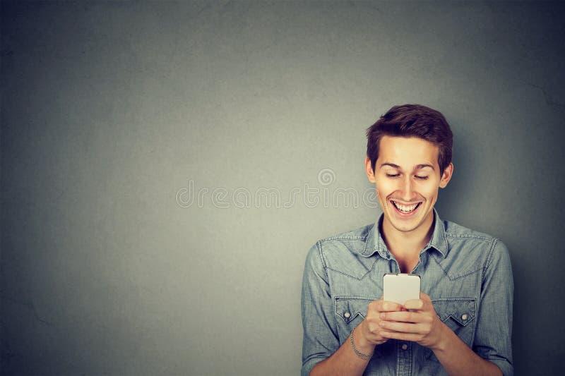 Individuo feliz hermoso que usa un smartphone imagen de archivo