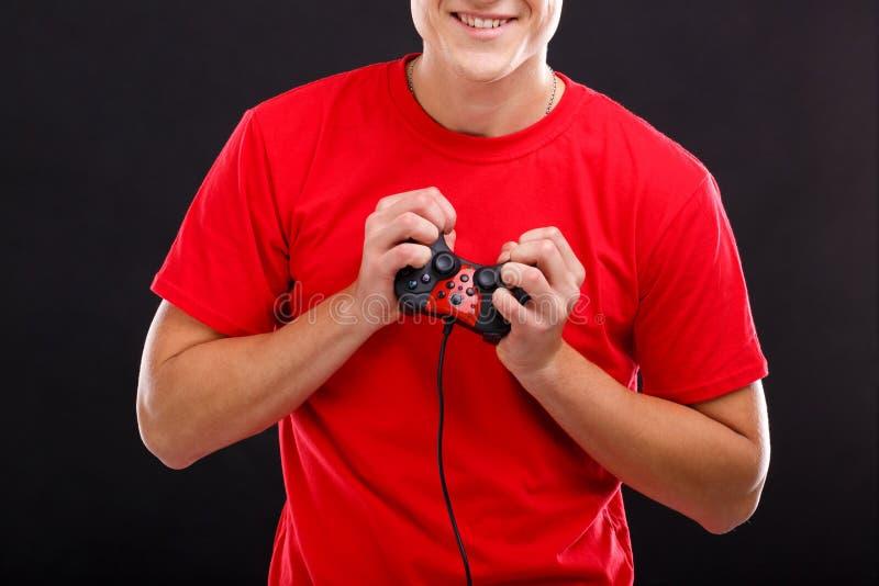 Individuo feliz que juega con una palanca de mando y una sonrisa del juego En un fondo negro Primer imagen de archivo libre de regalías