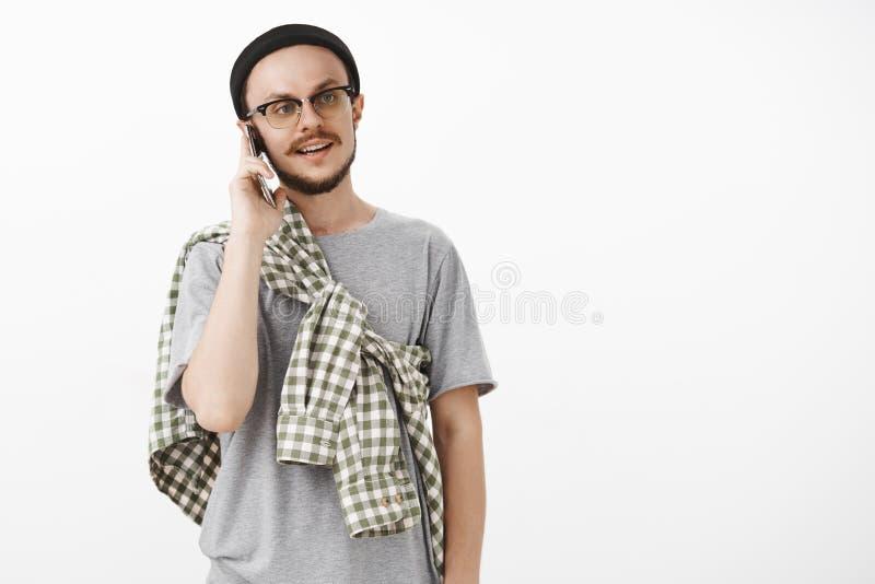 Individuo fresco del inconformista que llama a los compañeros que invitan para venir de visita y para asir smartphone de la tenen foto de archivo