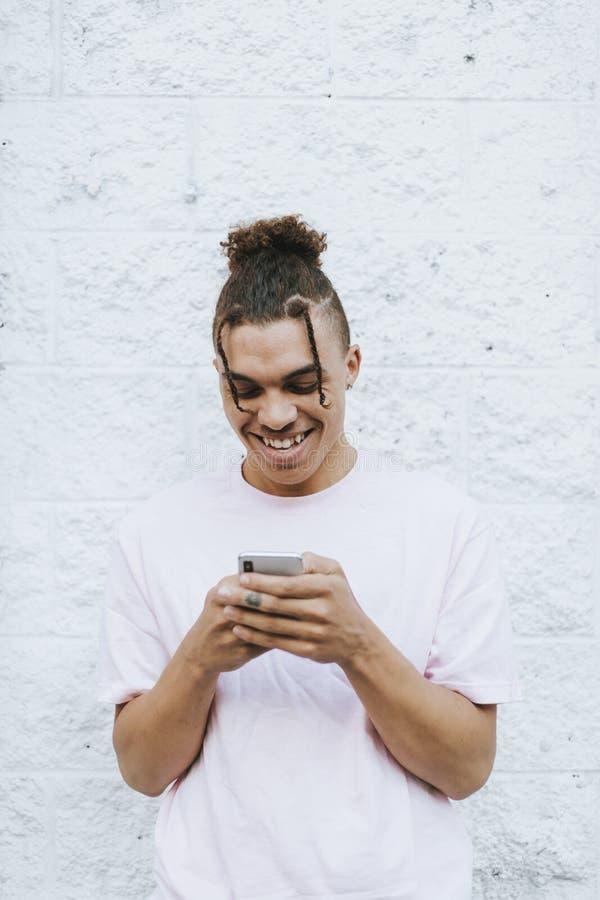 Individuo fresco que manda un SMS en su teléfono foto de archivo libre de regalías
